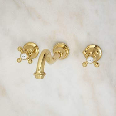 Wall-mounted brass faucet in three separate pieces with criss-cross hot/cold handles