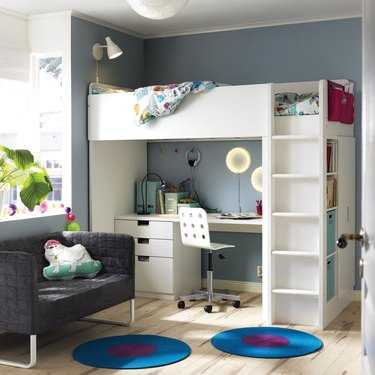 Bedroom display with raised bed and enclosed desk.