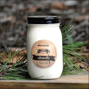 A black-and-cream mason jar with a citronella candle label.
