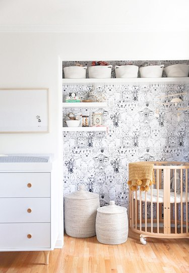 Nursery with wallpaper in nook, round crib, baskets, shelves, white dresser.