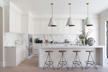modern white kitchen with sculptural bar stools and conical pendant lights
