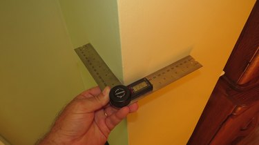 Digital protractor being used on an outside wall corner.