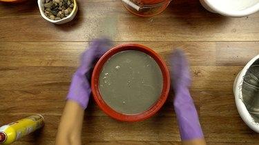Agitating concrete mix to release bubbles for DIY tabletop concrete fire bowl.