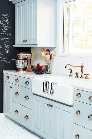 farmhouse kitchen with blue cabinets and brass hardware