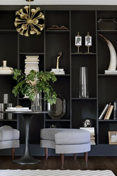 How To Organize a Bookshelf in room with Dark gray built in shelving, art, plant, curved gray benches, bistro table, modern pendant lamp, books.
