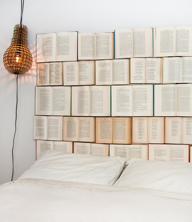 Opened books nailed to the wall serve as a headboard for a white bed.