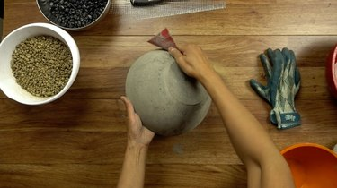 Sanding a newly-formed concrete bowl.