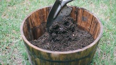 Filling a barrel planter with potting soil