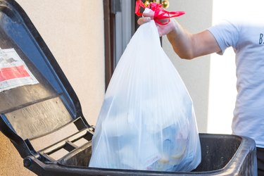 Bag of trash being removed from garbage can.