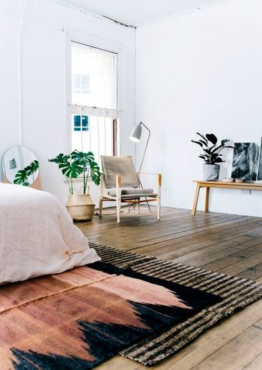 Layered rugs in mid-century bedroom