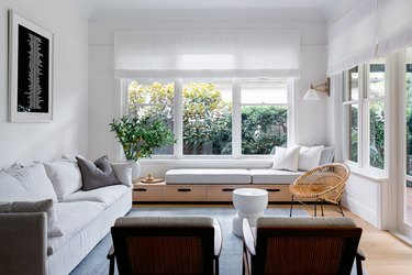 A white-walled living room with big windows, a white couch and linen curtains.