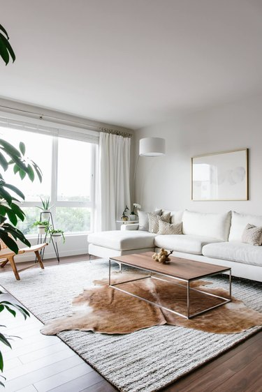 All white living room with layered rugs and large windows.