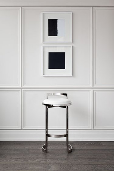 white wainscoted wall with silver barstool pictured