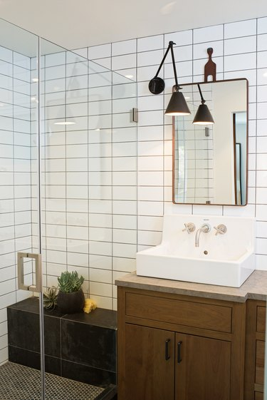 Photo of bathroom with glass walk-in shower with a bench.