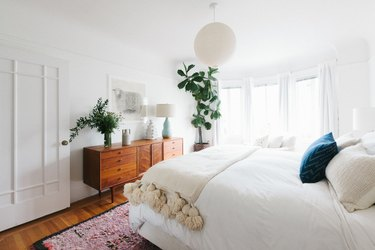 Bedroom featuring midcentury credenza and pom-pom throw blanket