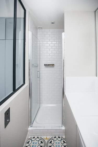 Photo of bathroom with narrow walk-in shower.