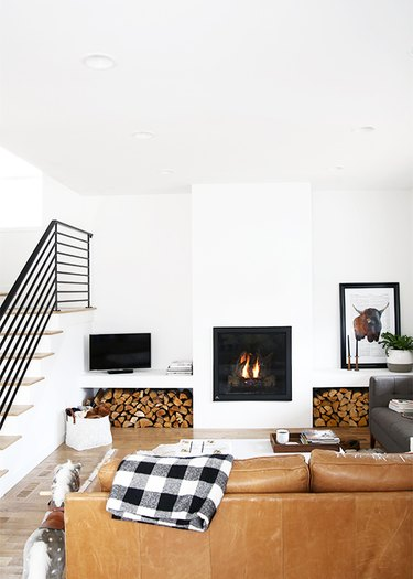 A leather couch faces a white wall with a fireplace and two sets of stacked logs.