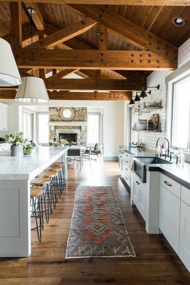 farmhouse kitchen with exposed ceiling beams and runner in front of sink