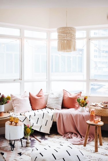 A bench streches across a wide corner window with pink and patterned blankets.