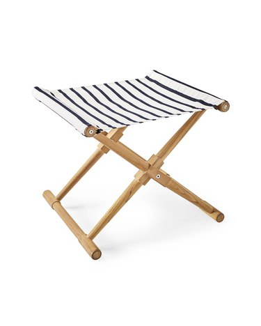 A teak-legged camp stool with a striped blue-and-white seat.