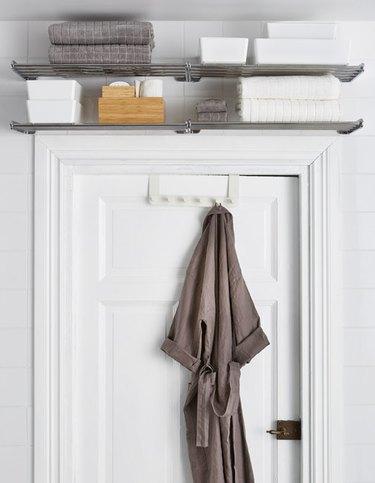 metal rack mounted above bathroom door.