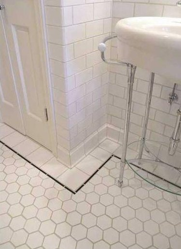 white sanitary cove base tile in white tiled bathroom black tile trim