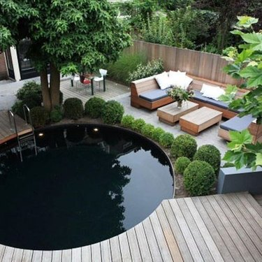 patio with round swimming pool and wooden deck