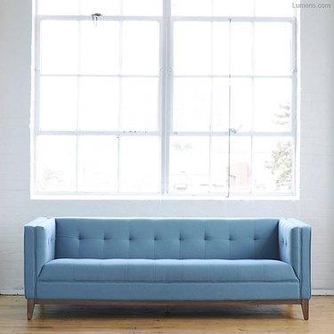A blue sofa beneath a large sunny window.