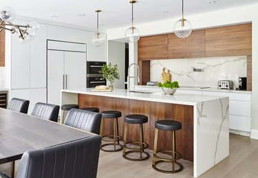 L-shaped kitchen with wood cabinets and waterfall countertop