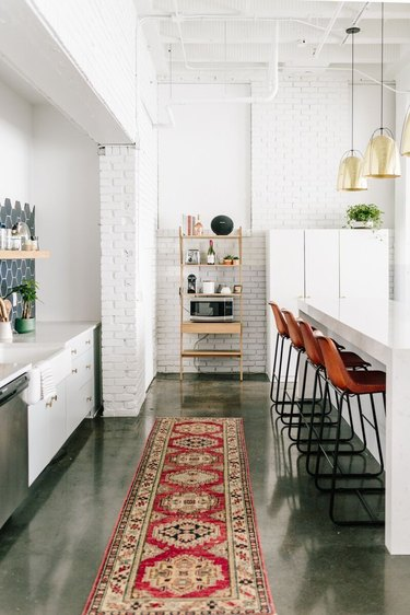 An open kitchen with white-brick walls and a concrete floor.