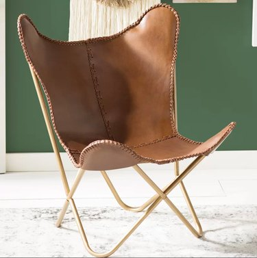A leather butterfly chair with gold frame.