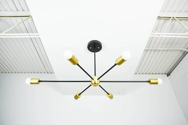 Modern black chandelier with six long arms and brass details