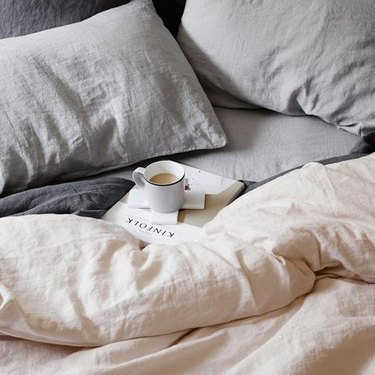 Blush and gray linens on a bed.