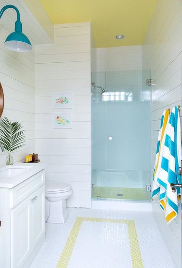 Photo of bathroom with blue glass walk-in shower.