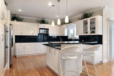 white cabinets, black granite countertops and backsplash, stainless steel appliances