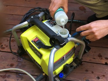 Filling a power washer with deck cleaning detergent.