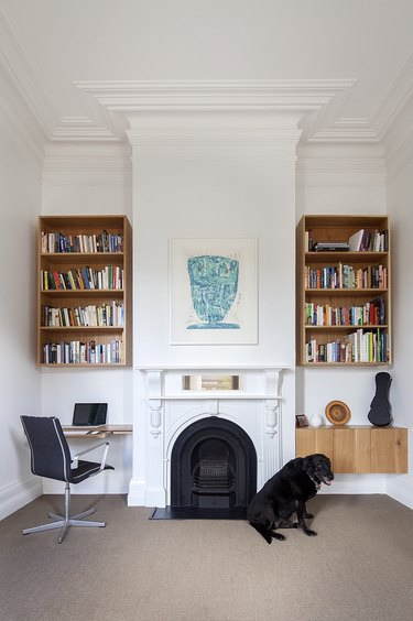 white home office with traditional fireplace and shelving on both sides