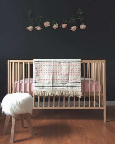 wood crib with pink bedding