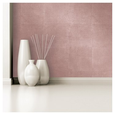 White vases before a rose-gold wallpaper.