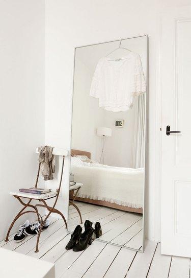 leaning floor mirror in minimalist room