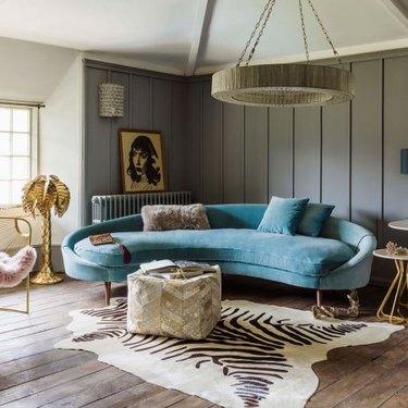 Retro room with turqouse velvet rounded sofa and zebra rug
