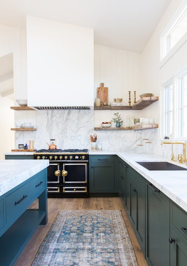 L-shaped kitchen with blue cabinets and marble countertops