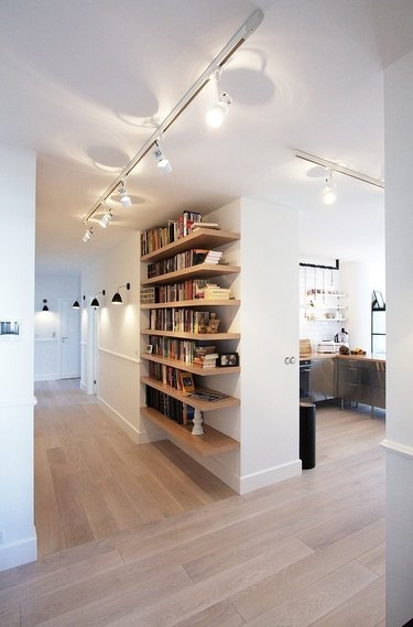 Modern Hallway with shelving, track lighting, wood floors, books.