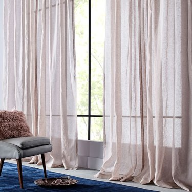 Blush curtains hang next to a gray chair and blue rug.