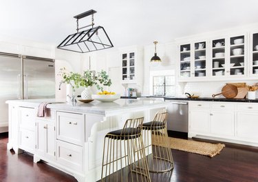 L-shaped kitchen design with white cabinets and black countertops