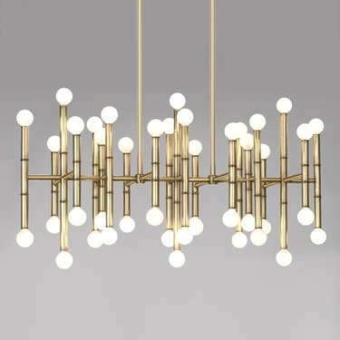 Modern chandelier featuring multiple vertical brass poles and small white circular bulbs