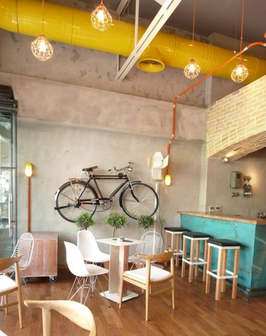 Urban living room with yellow painted pipe in ceiling