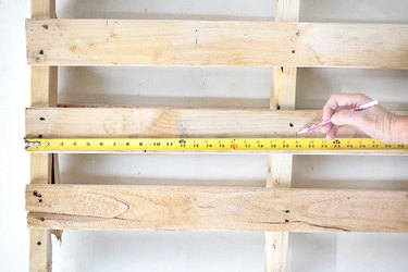 Pallet wood with measuring tape and hand marking measurement.