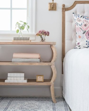 Farmhouse Chic Bedroom Ideas with decorative rug, table with shelves, bed with upholstered headboard.