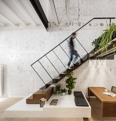white brick house with floating stairs and desk underneath